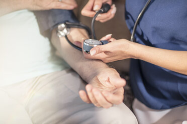 Nurse taking blood pressure of senior patient at home - ZEF14785