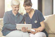 Senior woman sharing tablet with nurse at home - ZEF14788