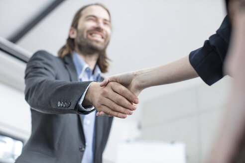 Businessman and businesswoman shaking hands in office - ZEF14803