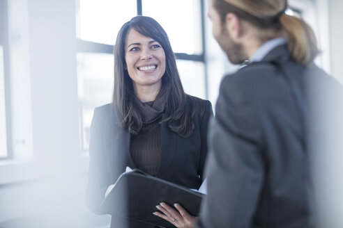 Businessman and businesswoman talking in office - ZEF14812