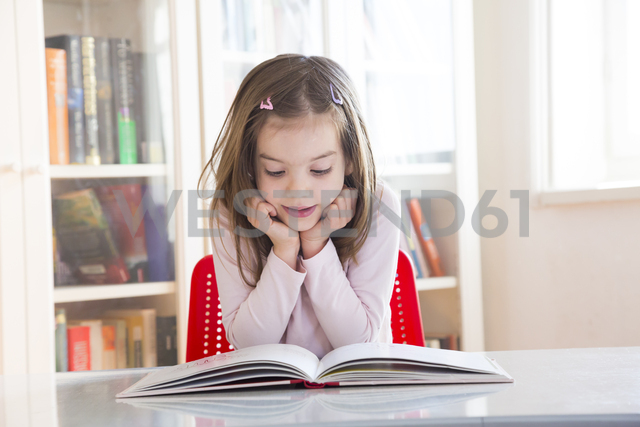 Portrait of little girl at table reading a book - LVF06418 - Larissa Veronesi/Westend61