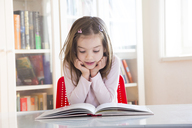 Portrait of little girl at table reading a book - LVF06418