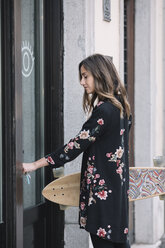 Fashionable woman with skateboard unlocking entrance door of her shop - ALBF00229