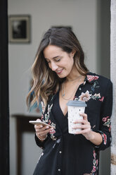 Portrait of smiling woman with coffee to go looking at cell phone - ALBF00232