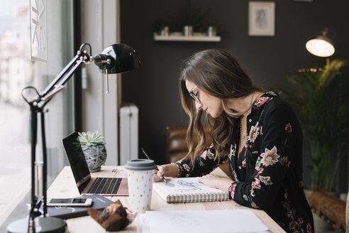 Woman drawing in sketch book at desk in tattoo studio - ALBF00238
