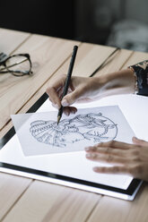 Woman's hand drawing template on light table - ALBF00247