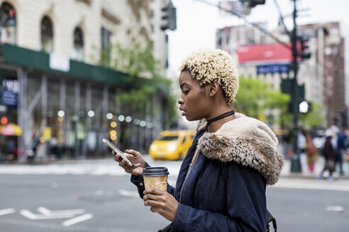 USA, New York City, fashionable young woman with coffee to go looking at cell phone on the street - MAUF01216