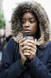 Portrait of fashionable young woman with coffee to go wearing hooded jacket - MAUF01219