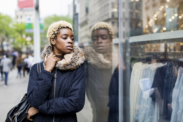 Portrait of young woman leaning against shop window - MAUF01222