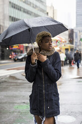 USA, New York City, portrait of young woman with umbrella on rainy day - MAUF01225