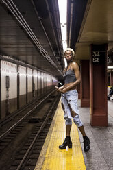 USA, New York City, portrait of woman waiting on subway station platform - MAUF01228
