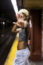 USA, New York City, woman on subway station platform showing hand palm - MAUF01231