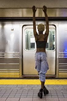 USA, New York City, back view of woman standing on subway station platform - MAUF01234