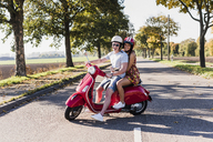 Portrait of happy young couple on motor scooter on country road - UUF12264
