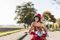 Happy young woman riding motor scooter on country road - UUF12273