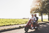 Happy young couple riding motor scooter on country road - UUF12279