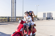 Happy young couple taking a selfie on motor scooter on parking level - UUF12282