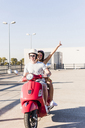 Carefree young couple riding motor scooter on parking level - UUF12285