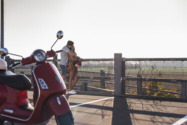 Young couple kissing on parking level with motor scooter in foreground - UUF12291