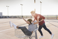 Playful young couple with shopping cart on parking level - UUF12297