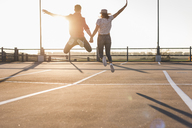 Carefree young couple jumping on parking levelat sunset - UUF12300