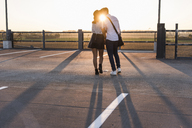 Young couple kissing on parking level at sunset - UUF12306