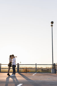 Young couple kissing on parking level at sunset - UUF12309