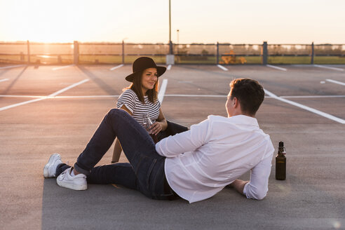 Young couple sitting on parking level at sunset with beer bottles - UUF12315