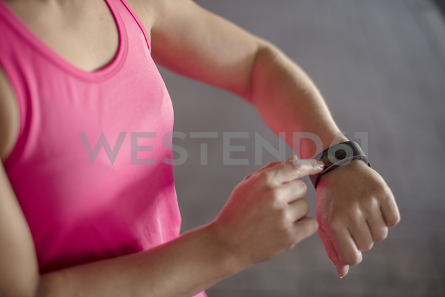 Woman adjustung settings of smartwatch for outdoor training - ZEF14826
