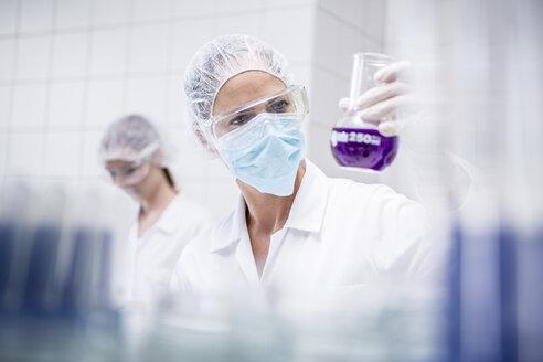 Scientist in lab examining liquid - WESTF23687