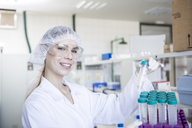 Portrait of smiling scientist in lab holding test tube - WESTF23735