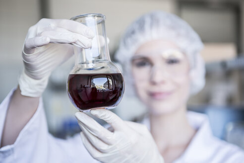 Scientist in lab holding flask with liquid - WESTF23738
