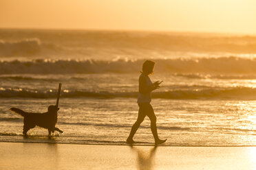 Indonesia, Bali, silhouette of woman walking with her dog on the beach at sunset - KNTF00919