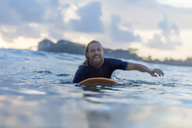 Portrait of happy man lying on surfboard on the sea - KNTF00925