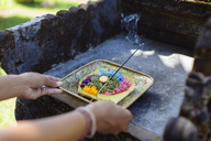 Woman serving Balinese offering - KNTF00928