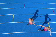 Top view of two female runners passing the baton on tartan track - STSF01423