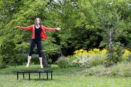 Laughing woman jumping on trampoline in the garden - NDF00694