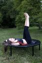 Woman lying on trampoline in the garden relaxing - NDF00697