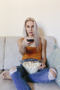 Young woman sitting on couch at home with bowl of popcorn and remote control - GIOF03355