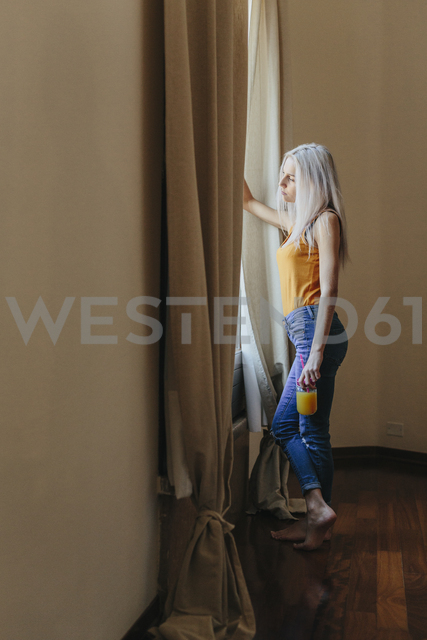 Young woman standing at the window at home - GIOF03358