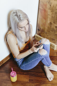 Young woman sitting on the floor at home using smartphone - GIOF03361