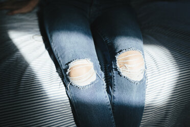 Close-up of woman sitting on bed at home wearing ripped jeans - GIOF03364