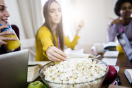 Female student with friends taking popcorn from bowl at table at home - GIOF03376