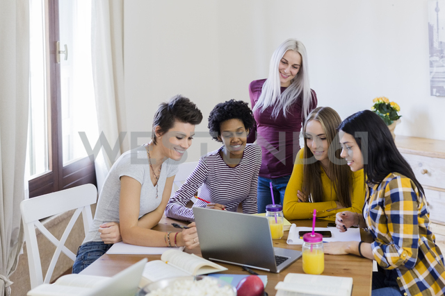 Group of female students sharing laptop at table at home - GIOF03385