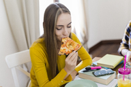 Young woman at home studying and having pizza - GIOF03397