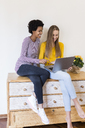 Two young women sitting on cupboard looking at laptop together - GIOF03412