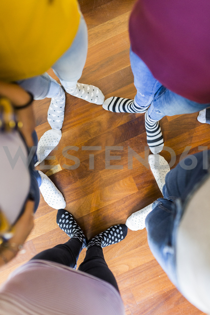 Close-up of feet of five women standing on wooden floor - GIOF03418