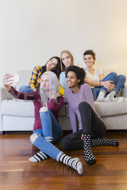 Happy female friends taking a selfie in living room - GIOF03424 - Giorgio Fochesato/Westend61