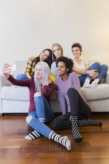 Happy female friends taking a selfie in living room - GIOF03424