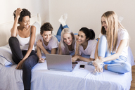 Happy female friends using laptop in bedroom - GIOF03430